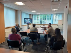 Staff group gather in-person and join online meeting